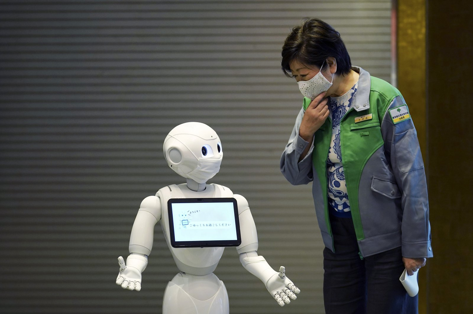 A humanoid robot Pepper wearing a face mask greets Tokyo Gov. Yuriko Koike at the lobby of a hotel for COVID-19 patients with mild symptoms during a media preview in Tokyo, Japan, Friday, May 1, 2020. (AP Photo)