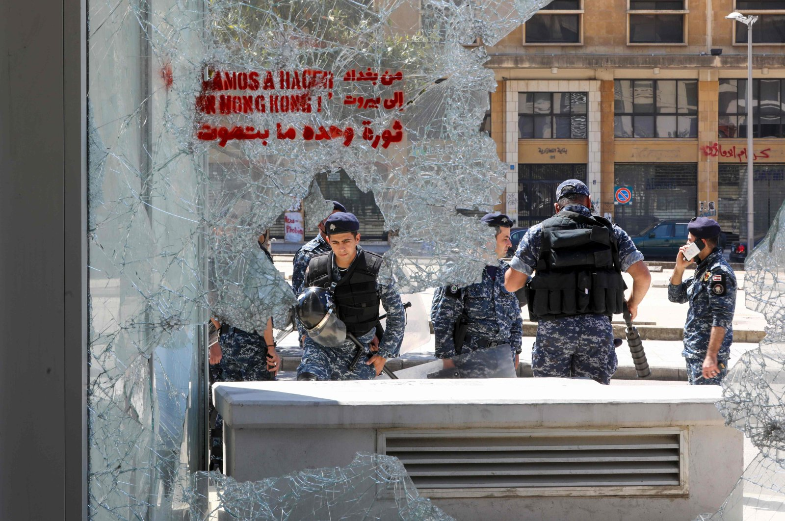 Members of the Lebanese security forces are seen through a broken store window in the downtown area of the capital Beirut, during an anti-government demonstration marking International Workers' Day (Labour Day), on May 1, 2020. (AFP Photo)