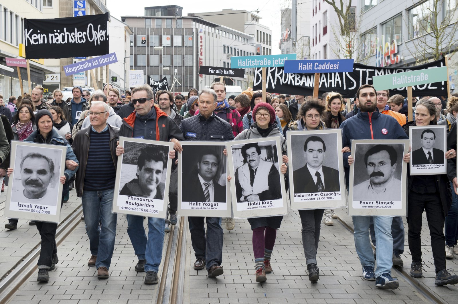 Demonstrators walk holding posters of people killed by NSU, in Kassel, Germany, Thursday, April 6, 2017. (AP Photo)