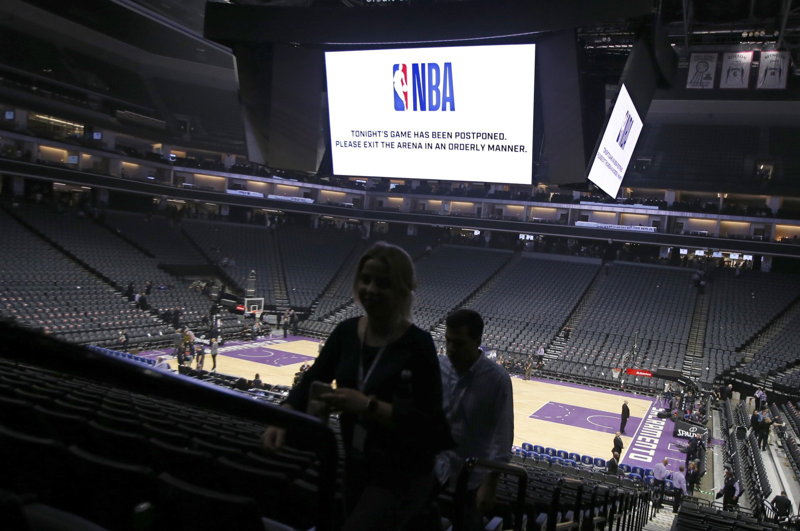 """Fans leave the Golden 1 Center after a NBA basketball game was postponed at the last minute over an """"abundance of caution"""" after a player tested positive for the coronavirus, Sacramento, United States, Wednesday, March 11, 2020. (AP Photo)"""