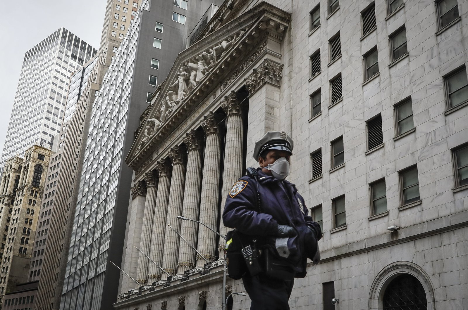An NYPD officer walks along a sparsely populated Wall Street, Friday, May 1, 2020, in the Manhattan borough of New York. (AP Photo)