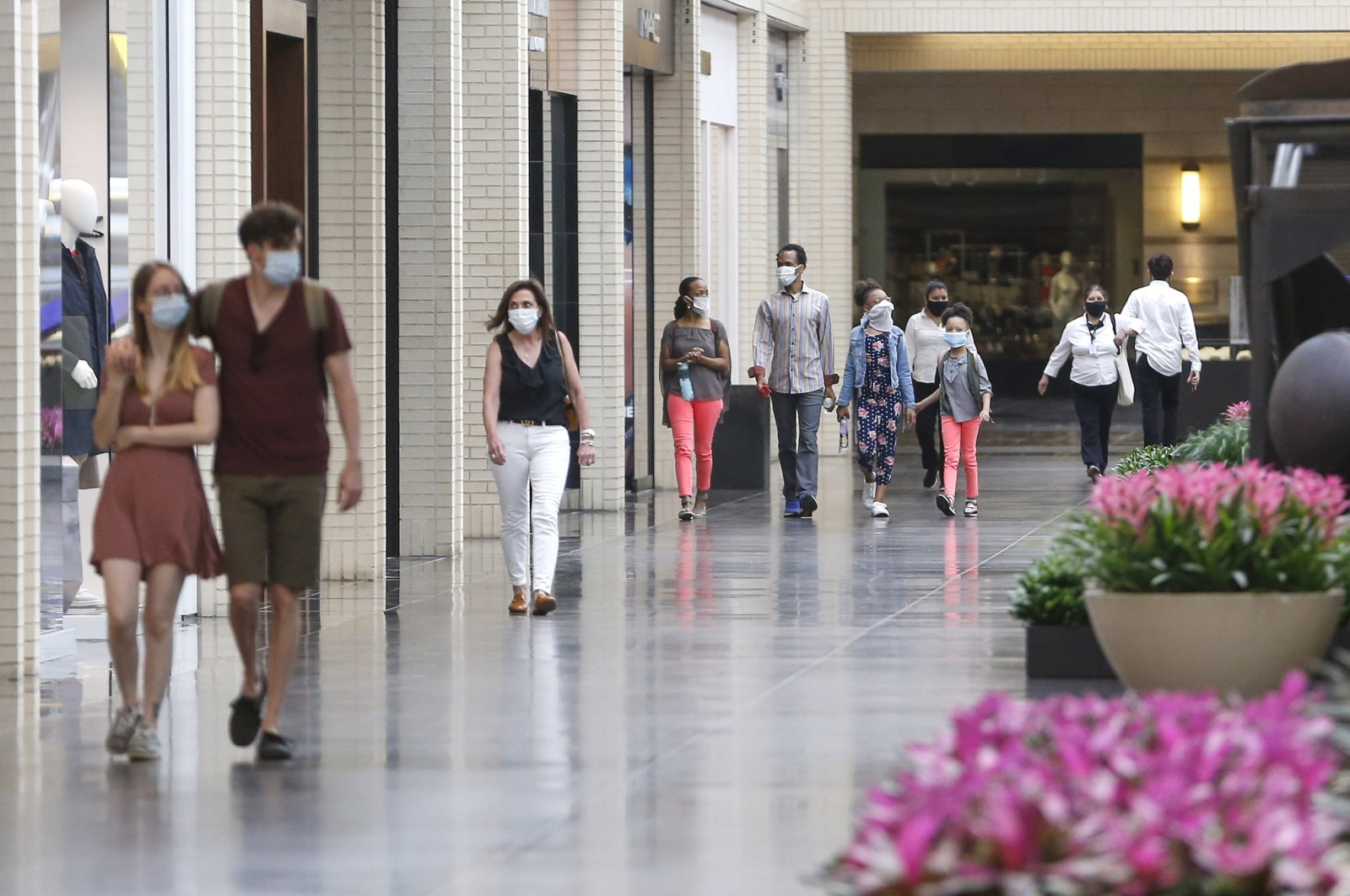 Shoppers walk through NorthPark Center mall on Friday, May 1, 2020 in Dallas, Texas. (The Dallas Morning News via AP)