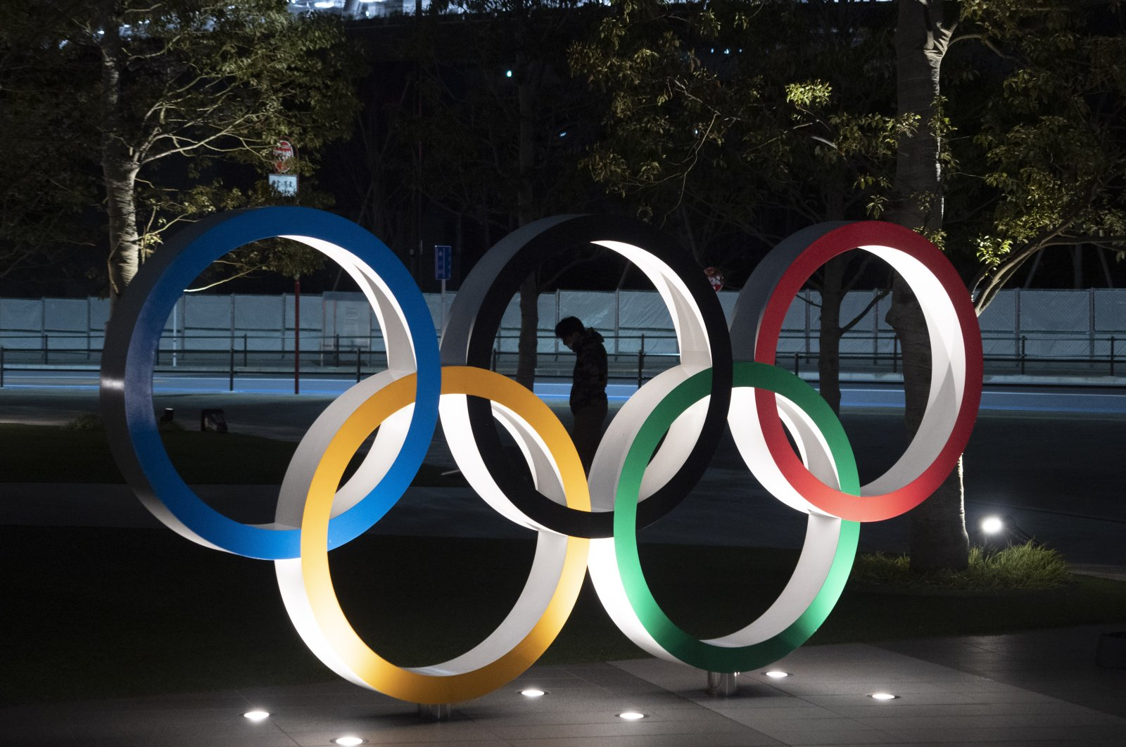 A man is seen through the Olympic rings in front of the New National Stadium in Tokyo, Japan on Tuesday, March 24, 2020. (AP Photo)
