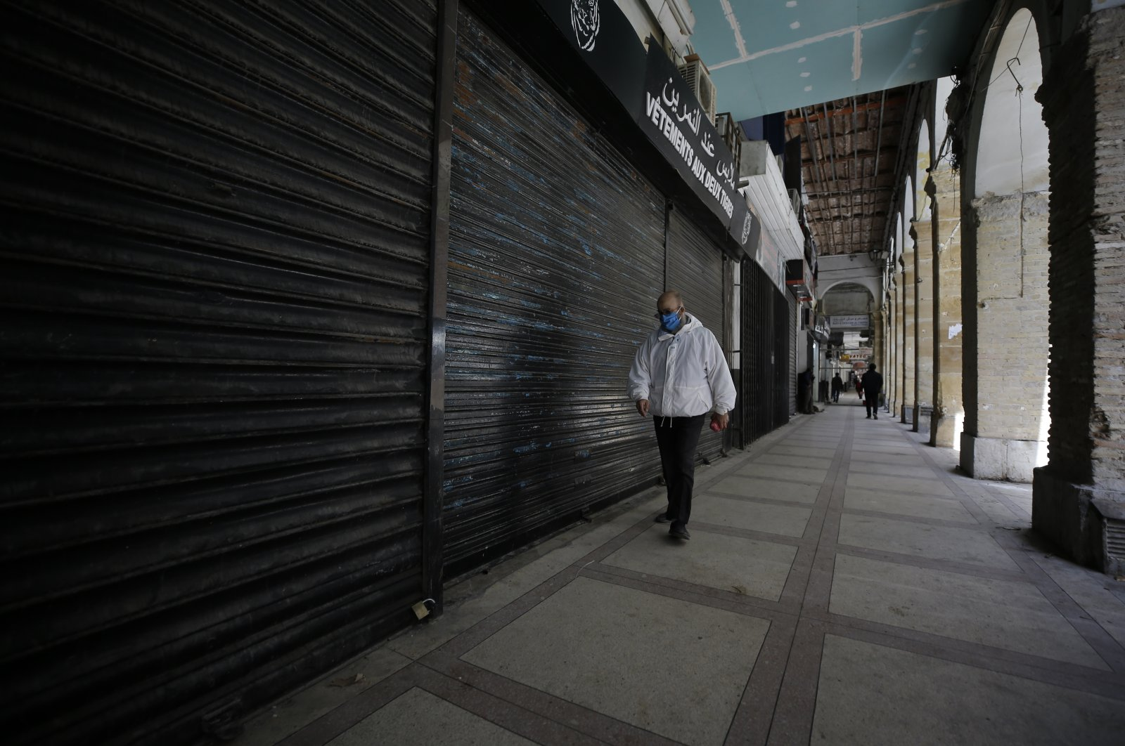 A man walks by closed shops in Algiers, Wednesday, April 29, 2020. (AP Photo)
