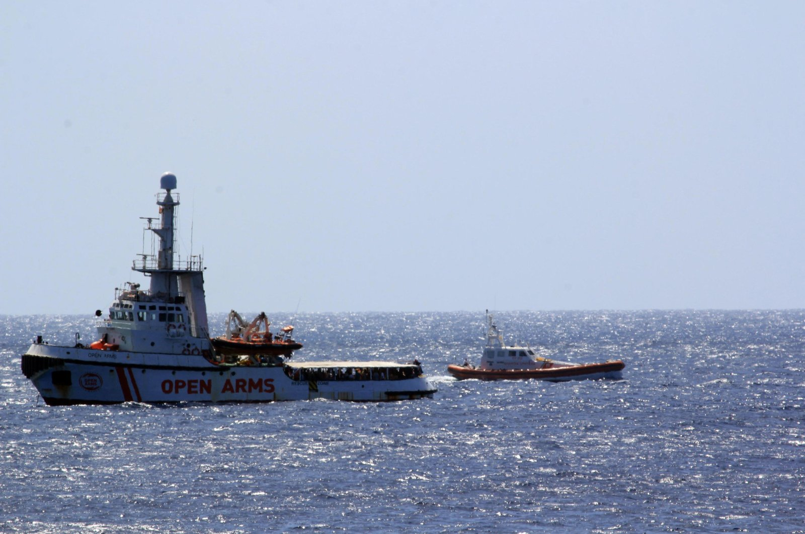 The Open Arms Spanish humanitarian boat with 147 migrants, left, is monitored by an Italian Coast guard vessel as it sails off the coasts of the Sicilian island of Lampedusa, southern Italy, Sunday, Aug. 15, 2019. (AP Photo)