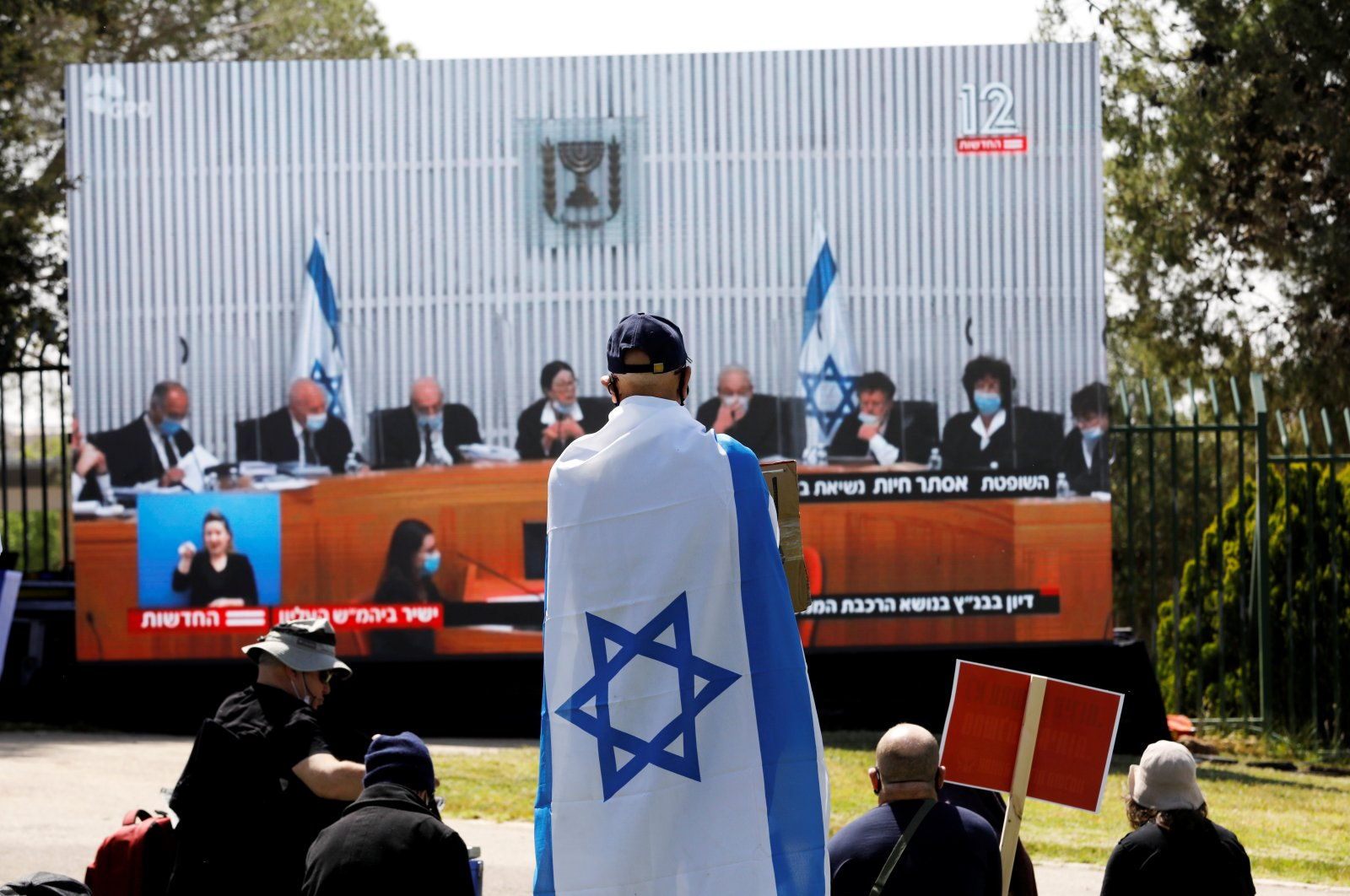 Israelis protest, in front of a placard with the photo of the High Court judges outside the Knesset against Prime minister Benjamin Netanyahu in Jerusalem, May 3, 2020. (Reuters Photo)