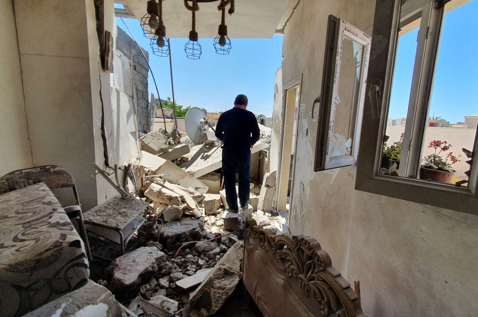 A resident walks amidst the rubble of a building that was damaged when forces loyal to putschist Gen. Khalifa Haftar shelled the residential neighborhood of Znatah in the Libyan capital Tripoli, held by the U.N.-recognized Government of National Accord (GNA), May 1, 2020. (AFP)