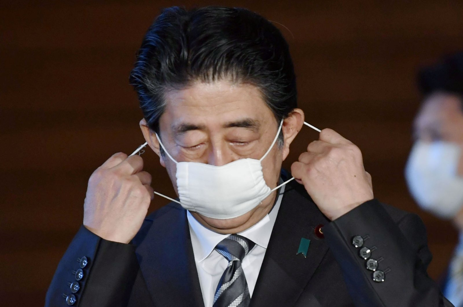 Japan's Prime Minister Shinzo Abe puts off his protective face mask as he speaks to media on Japan's response to the coronavirus disease (COVID-19) outbreak at his official residence in Tokyo, Japan, May 1, 2020, in this photo taken by Kyodo. (Reuters Photo)