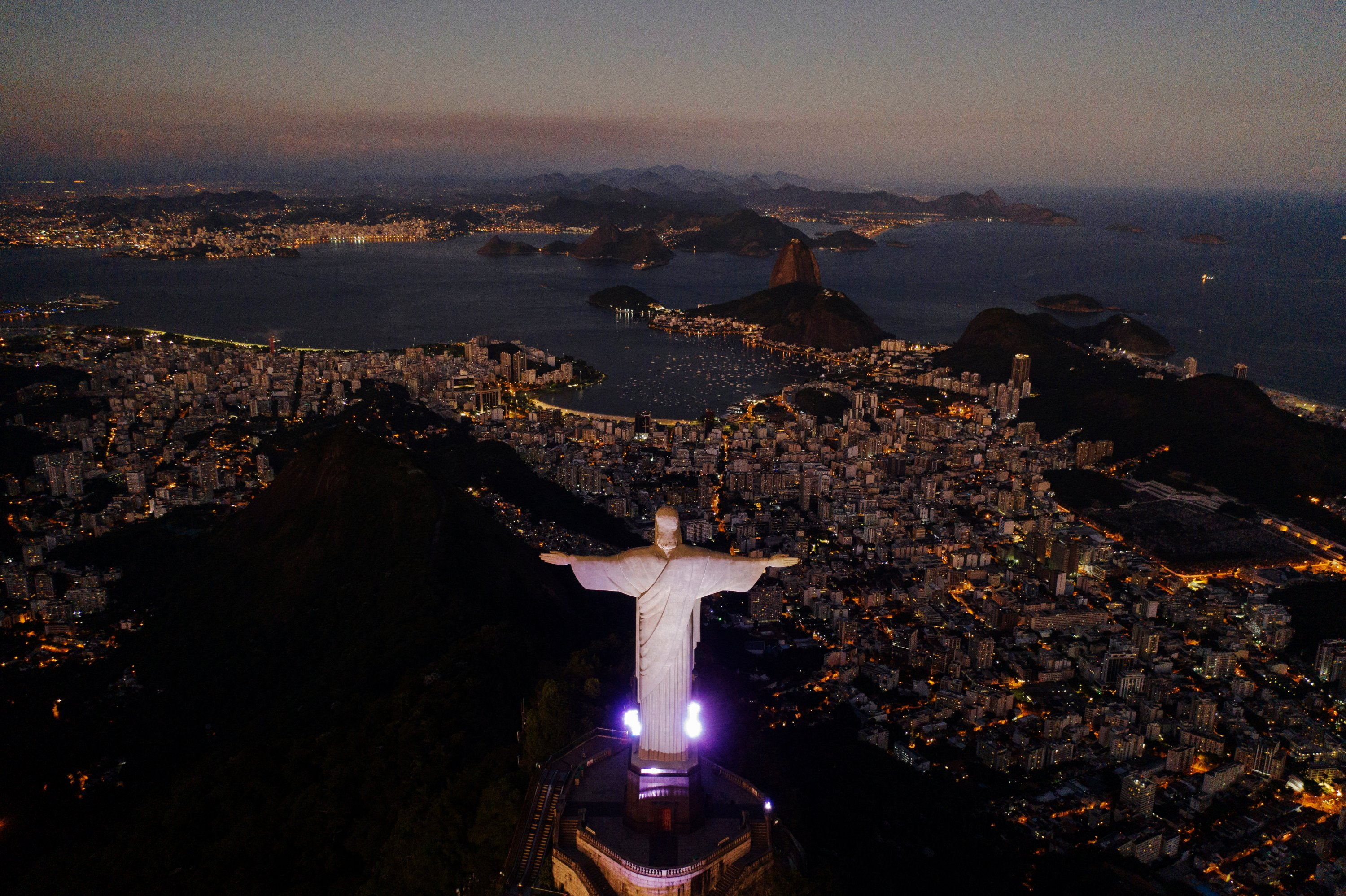 The Christ the Redeemer statue stands above the Guanabara bay during dusk amid the outbreak of the coronavirus in Rio de Janeiro, Brazil, Monday, April 27, 2020. (AP Photo)