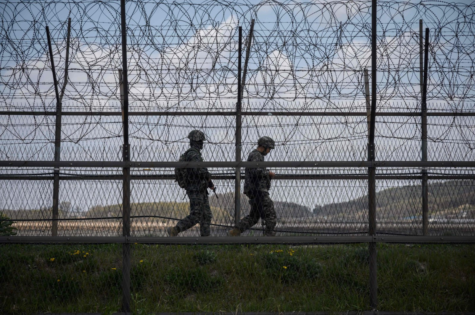 South Korean soldiers patrolling along a barbed wire fence Demilitarized Zone (DMZ) separating North and South Korea, on the South Korean island of Ganghwa, April 23, 2020. (AFP Photo)