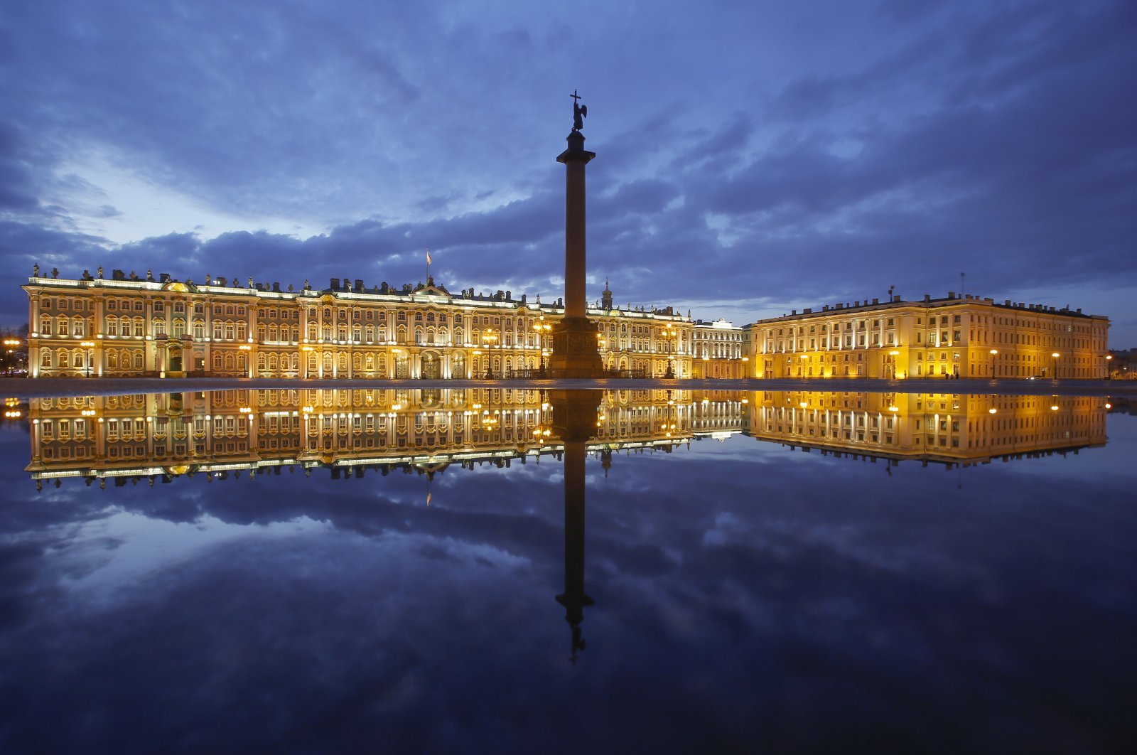 The Winter Palace and Alexander Column are reflected in a puddle after rain at Palace Square in St. Petersburg, Russia, Monday, April 27, 2020. (AP Photo)
