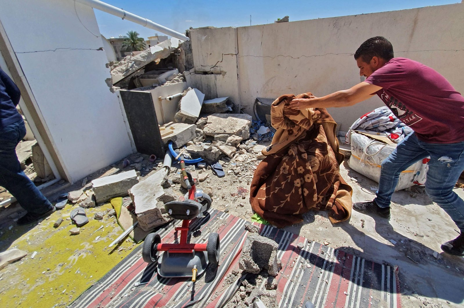 Residents salvage some belongings amidst the rubble of a building that was damaged when forces loyal to putschist Gen. Khalifa Haftar shelled the residential neighborhood of Znatah in the Libyan capital Tripoli,  May 1, 2020. (AFP)