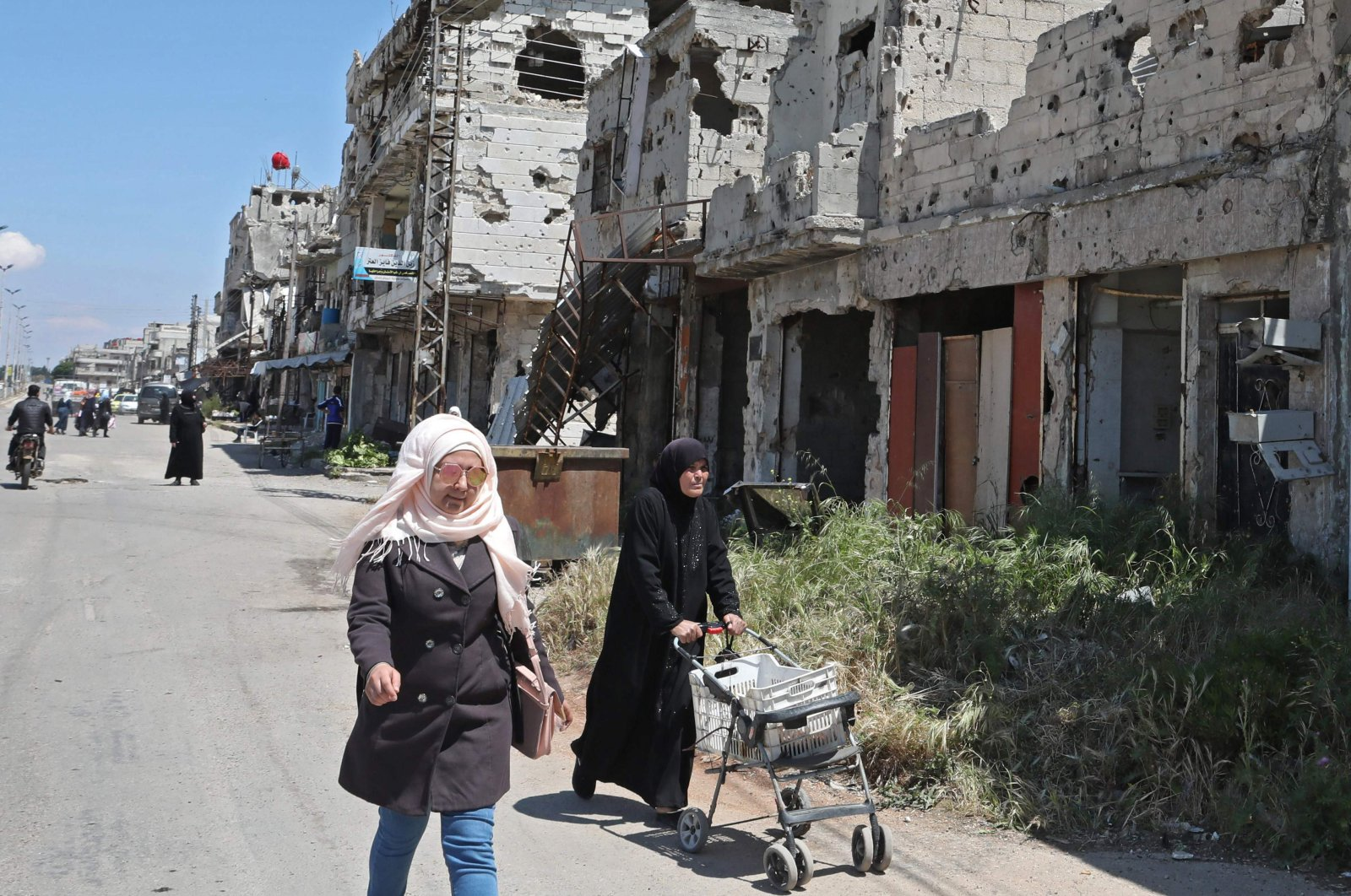 Syrians walk past buildings heavily damaged during Syria's civil war, in the central city of Homs, April 28, 2020. (AFP)