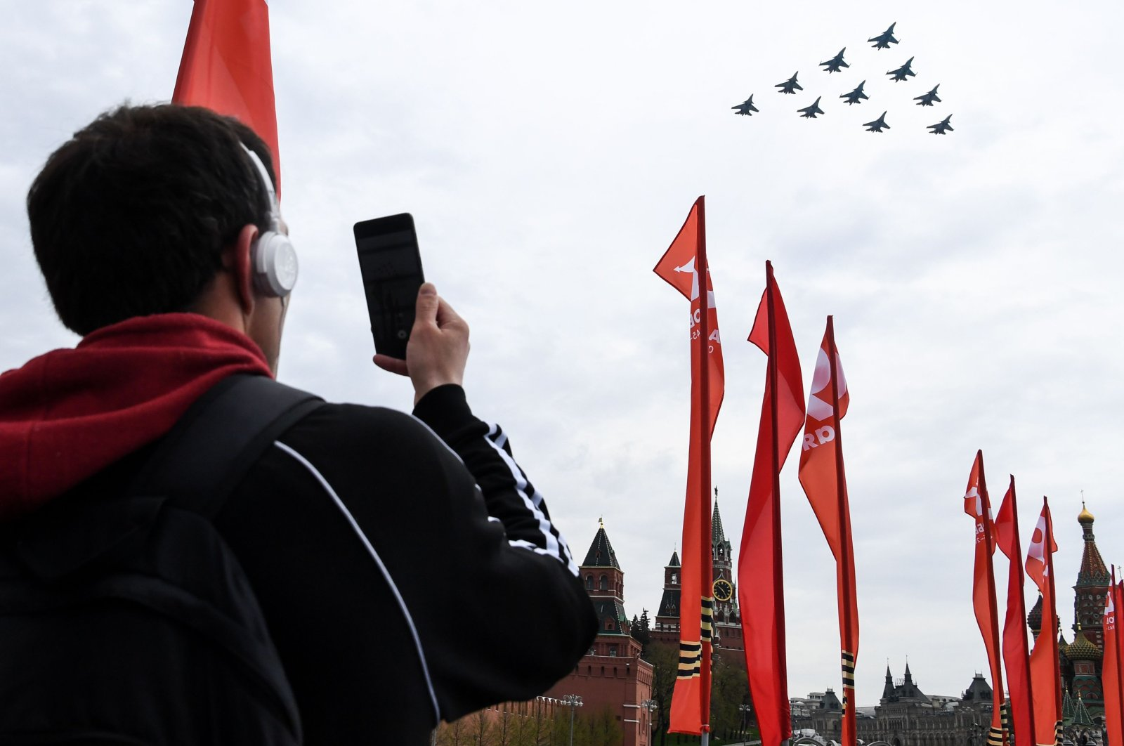 A man takes pictures with his mobile phone of Russian Su-34 fighter bombers, Su-30M jet fighters and Su-35 jet fighters flying over the Red Square during a rehearsal for the Victory Day military parade in Moscow on May 4, 2020. (AFP Photo)