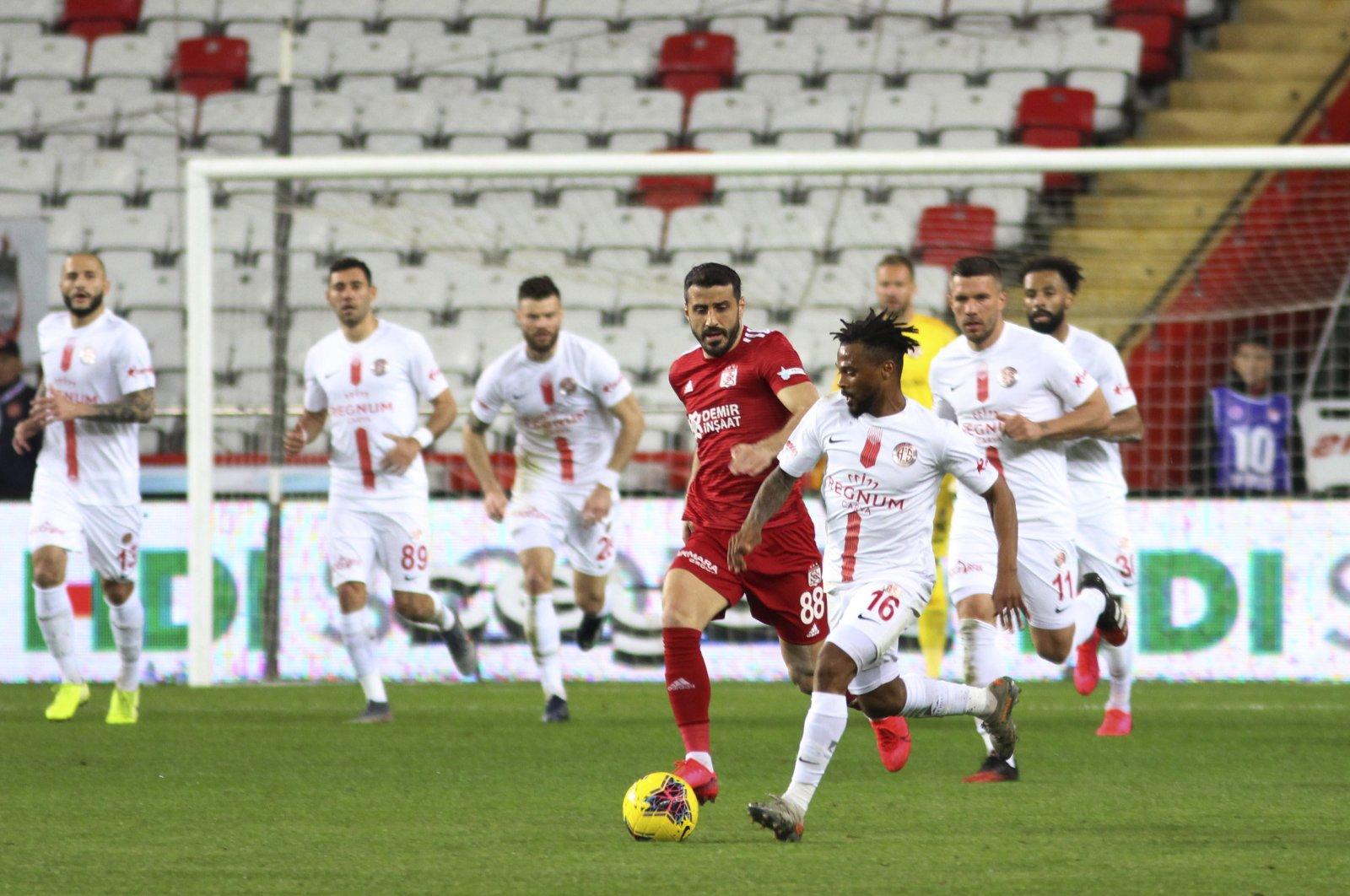 Antalyaspor's Alfredo Kulembe Ribeiro (R) controls the ball in front of Sivasspor's Caner Osmanpaşa during a Süper Lig match in Antalya, Turkey, March 16, 2020. (AP Photo)