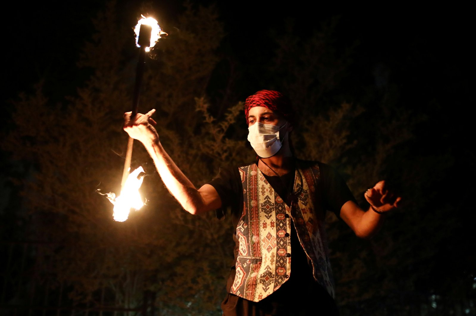 A man plays with fire next to a festive Ramadan float as it drives through a street in east Jerusalem to bring celebrations to people under the coronavirus-related movement restrictions, May 3, 2020. (Reuters)
