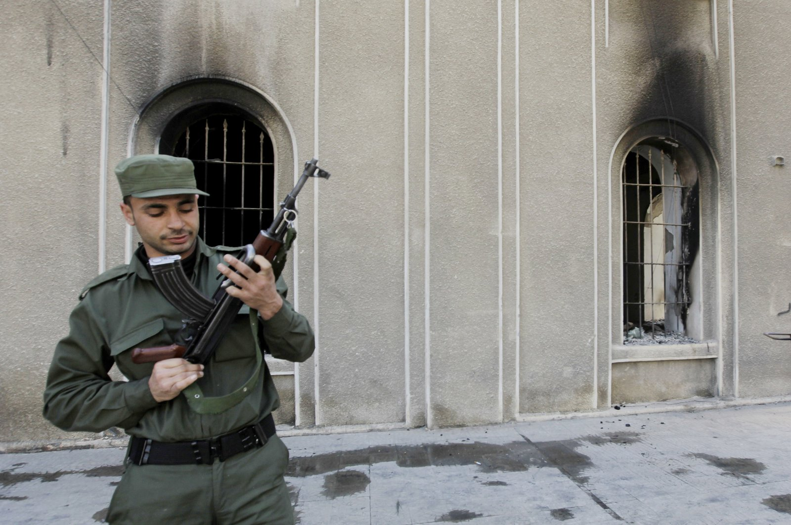 A Syrian regime soldier checks his AK-47 as he stands in front the burned court building that was set on fire by anti-regime protesters, in the southern city of Daraa, Syria, March 21, 2011. (AP Photo)