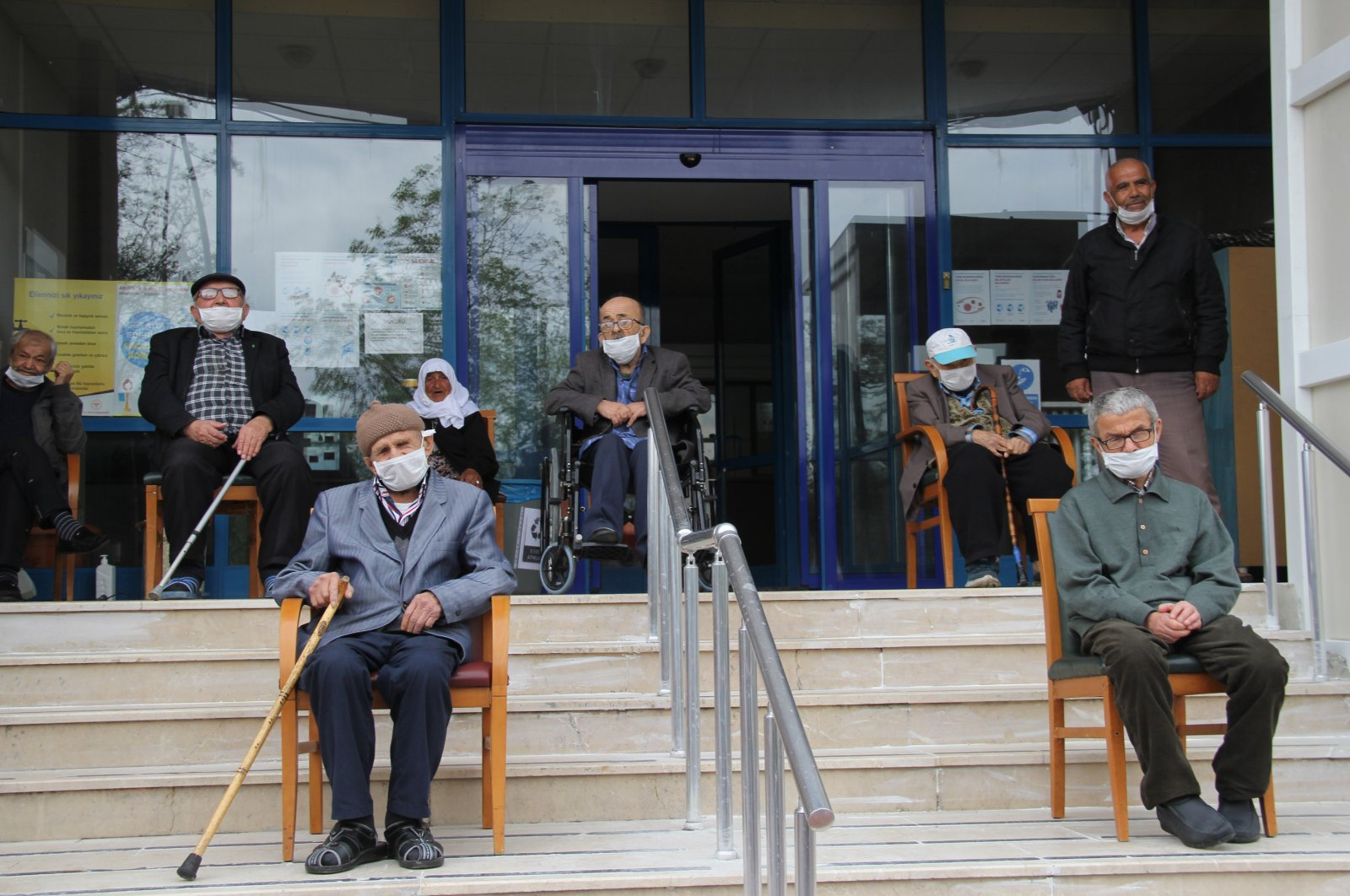 A group of nursing home residents wearing masks watch a concert in the courtyard, Karabük, Turkey, April 27, 2020. (İHA Photo)