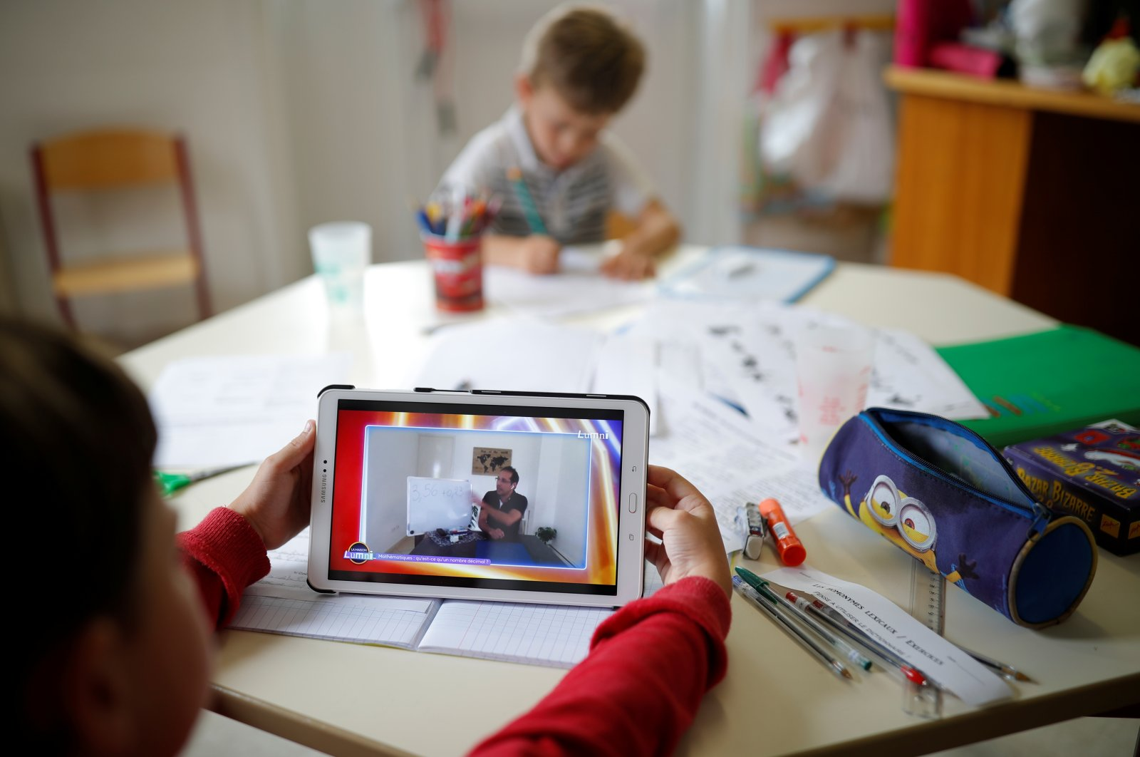 A pupil looks at a tablet to study with his teacher during an online school in a private school open to children of health workers and workers on the coronavirus frontline in Saint-Sebastien-sur-Loire near Nantes during the outbreak of the coronavirus disease (COVID-19) in France, May 4, 2020. (Reuters Photo)