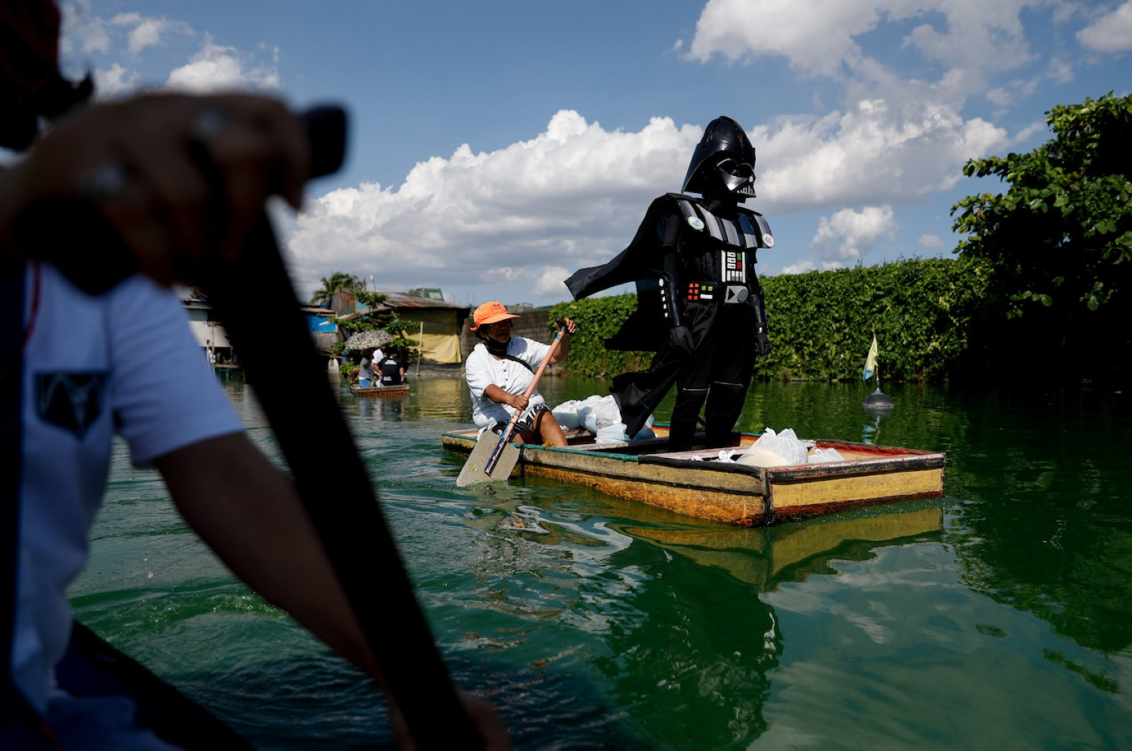 A village officer dressed as the Star Wars character Darth Vader rides a small boat to deliver relief goods to residents in the flooded Artex Compound in Malabon, Metro Manila, Philippines, May 4, 2020. REUTERS/Eloisa Lopez