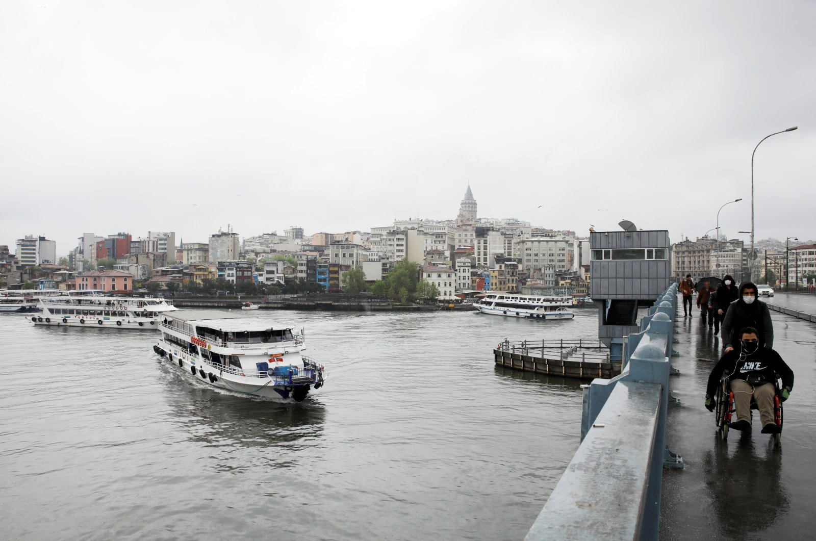 Boats sail along the Golden Horn and people walk on Galata Bridge, amid the coronavirus pandemic, in Istanbul, Turkey, May 4, 2020. (REUTERS Photo)