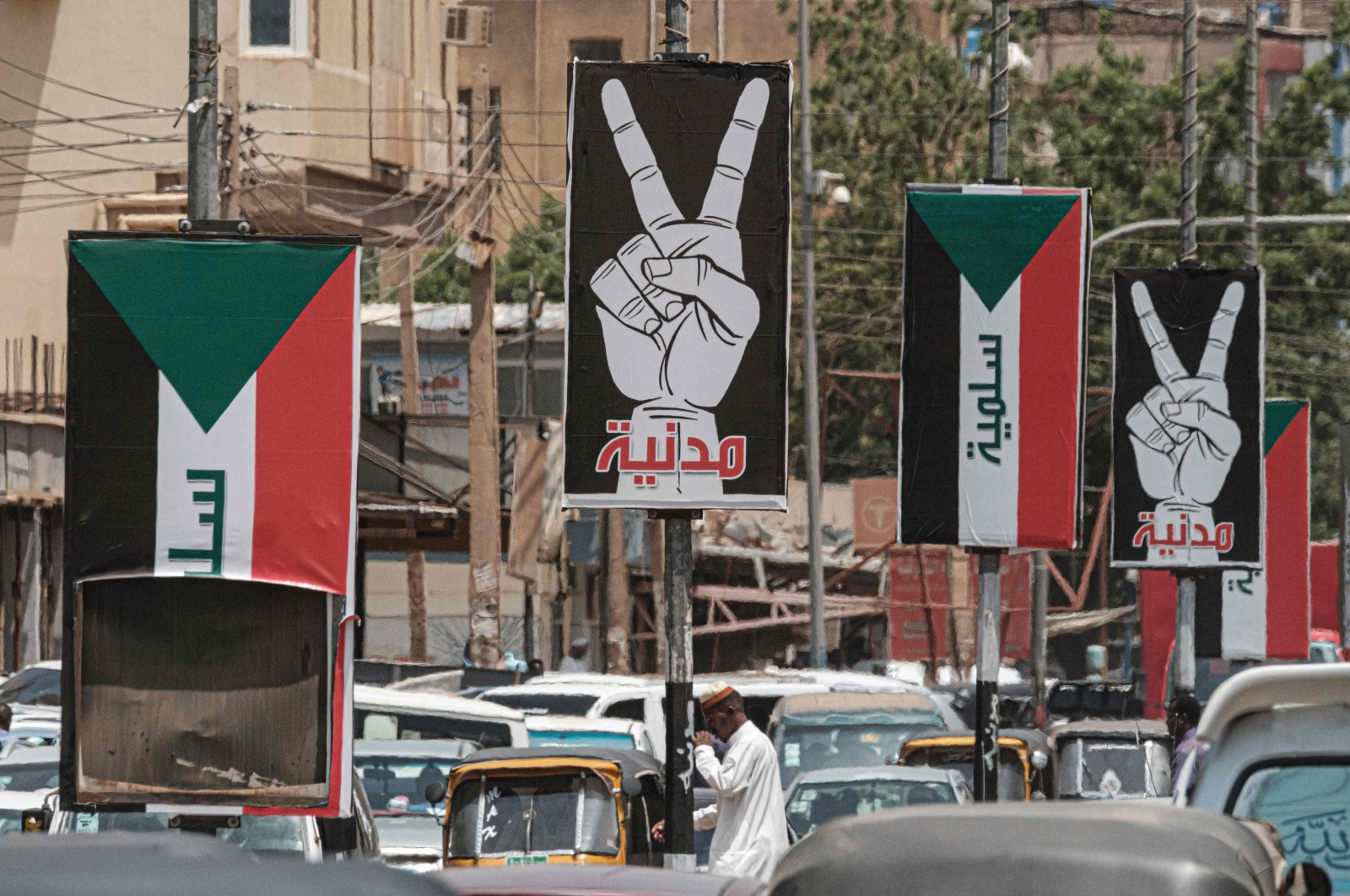 Placards showing the victory gesture with the Arabic word for civilian and others of the Sudanese flag with the word peaceful seen along a street in Khartoum, Sudan, June 15, 2019. (AFP Photo)