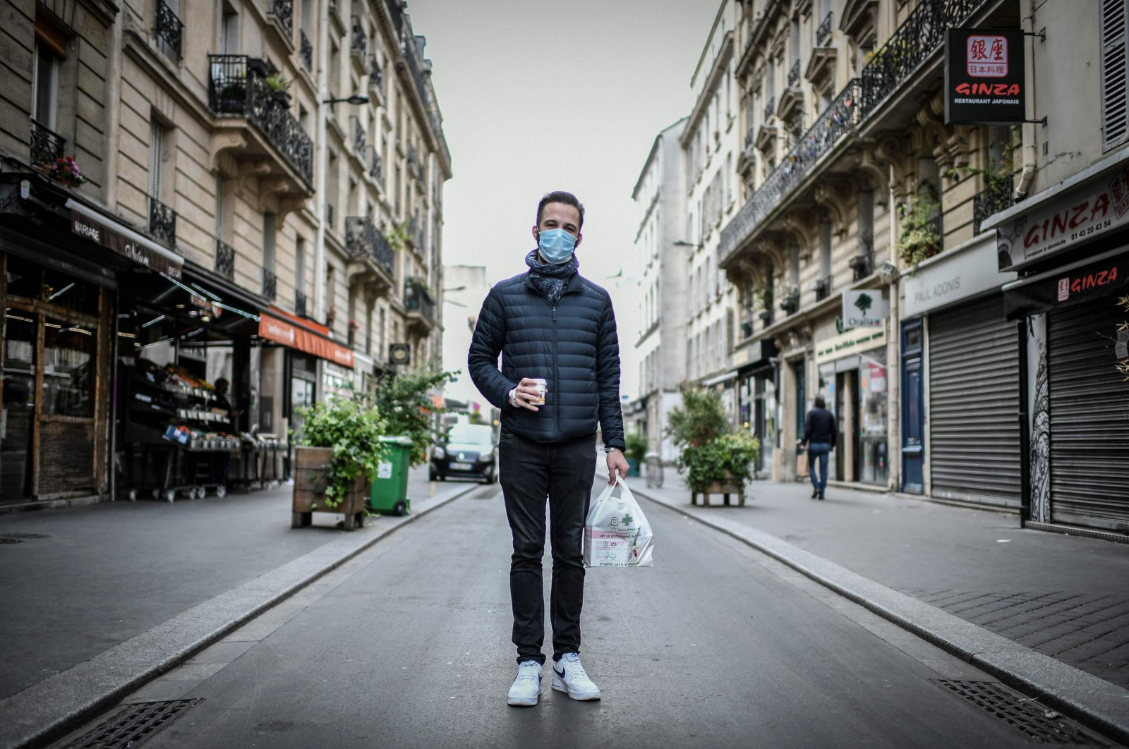 A man, wearing a protective face mask, poses for a photograph in the streets of Paris on May 4, 2020, (AFP Photo)