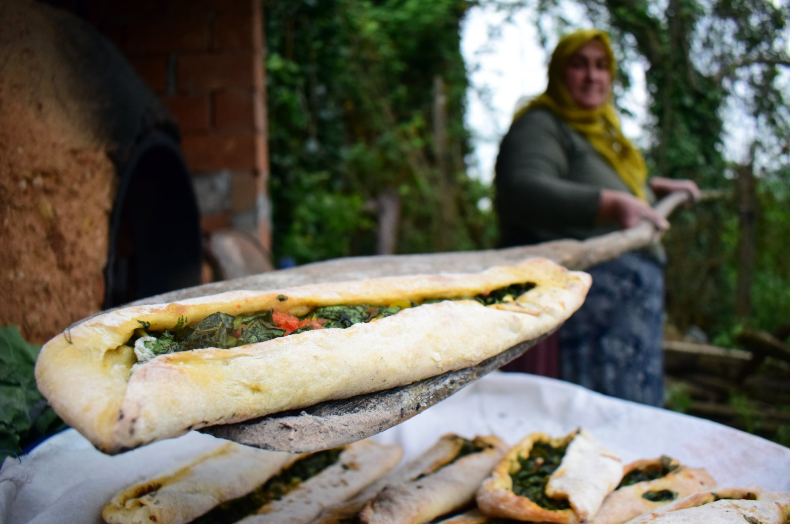 A woman takes a pide filled with collard greens from an earthen oven, in Çayağzı village, Düzce province, Turkey, April 26, 2020. (AA Photo)