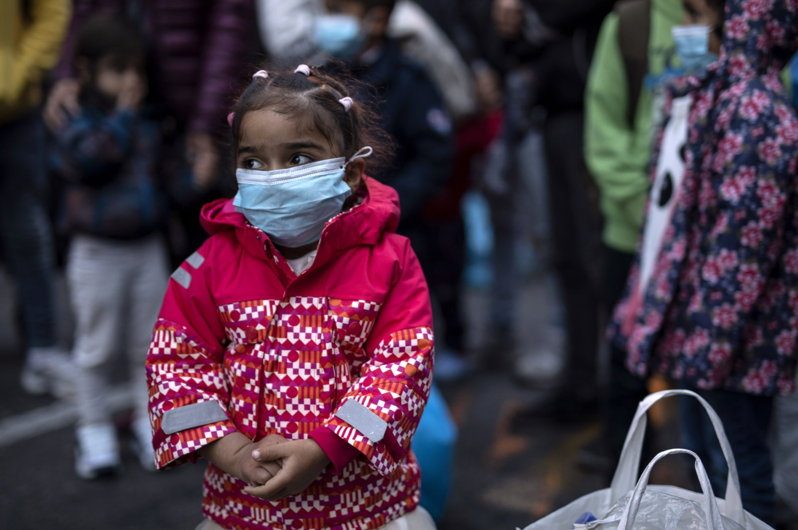 A young girl wearing a mask to prevent the spread of the coronavirus, looks on after refugees and migrants arrived at the port of Piraeus, near Athens, on Monday, May 4, 2020. (AP Photo)