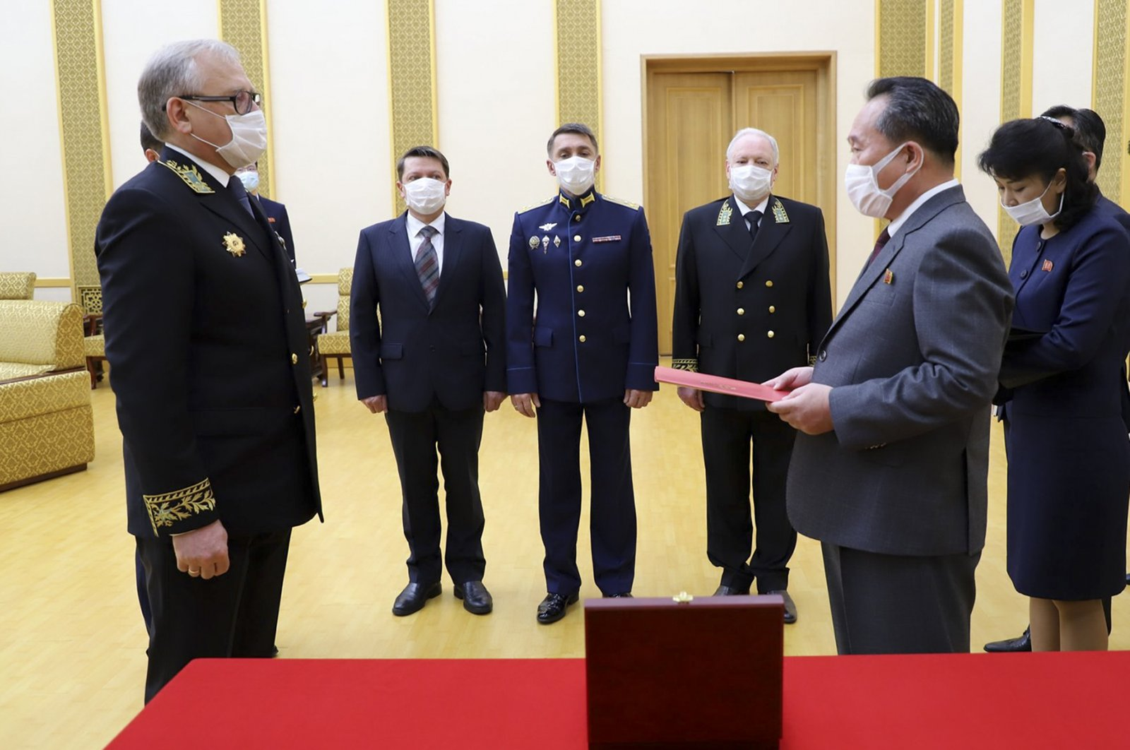 Russian Ambassador to the Democratic People's Republic of Korea Alexander Matsegora (L) and DPRK Foreign Minister Ri Son-gwon (R), both wearing face masks to protect against the novel coronavirus, attend a ceremony awarding North Korean leader Kim Jong-un with Russia's 75th anniversary Victory medal for his major contribution in commemorating Soviet soldiers, Pyongyang, North Korea, May 5, 2020. (AP Photo)