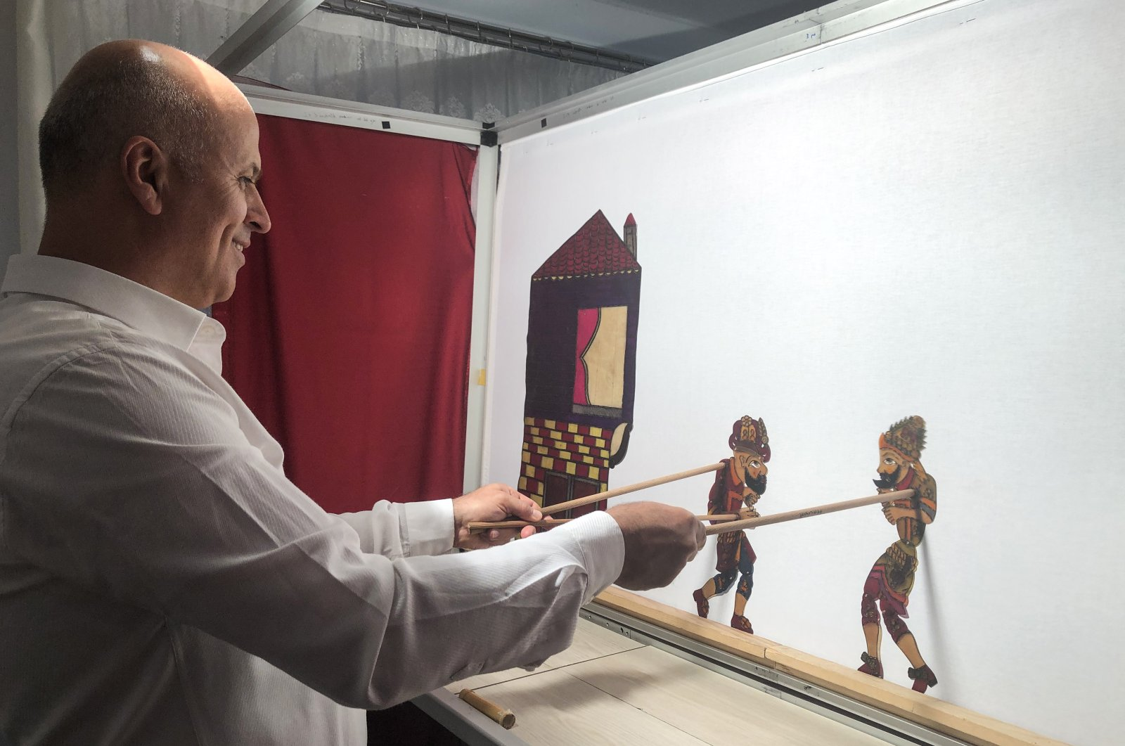 Suat Veral performs a shadow play with the Karagöz and Hacivat characters, in this undated photo. (AA Photo)
