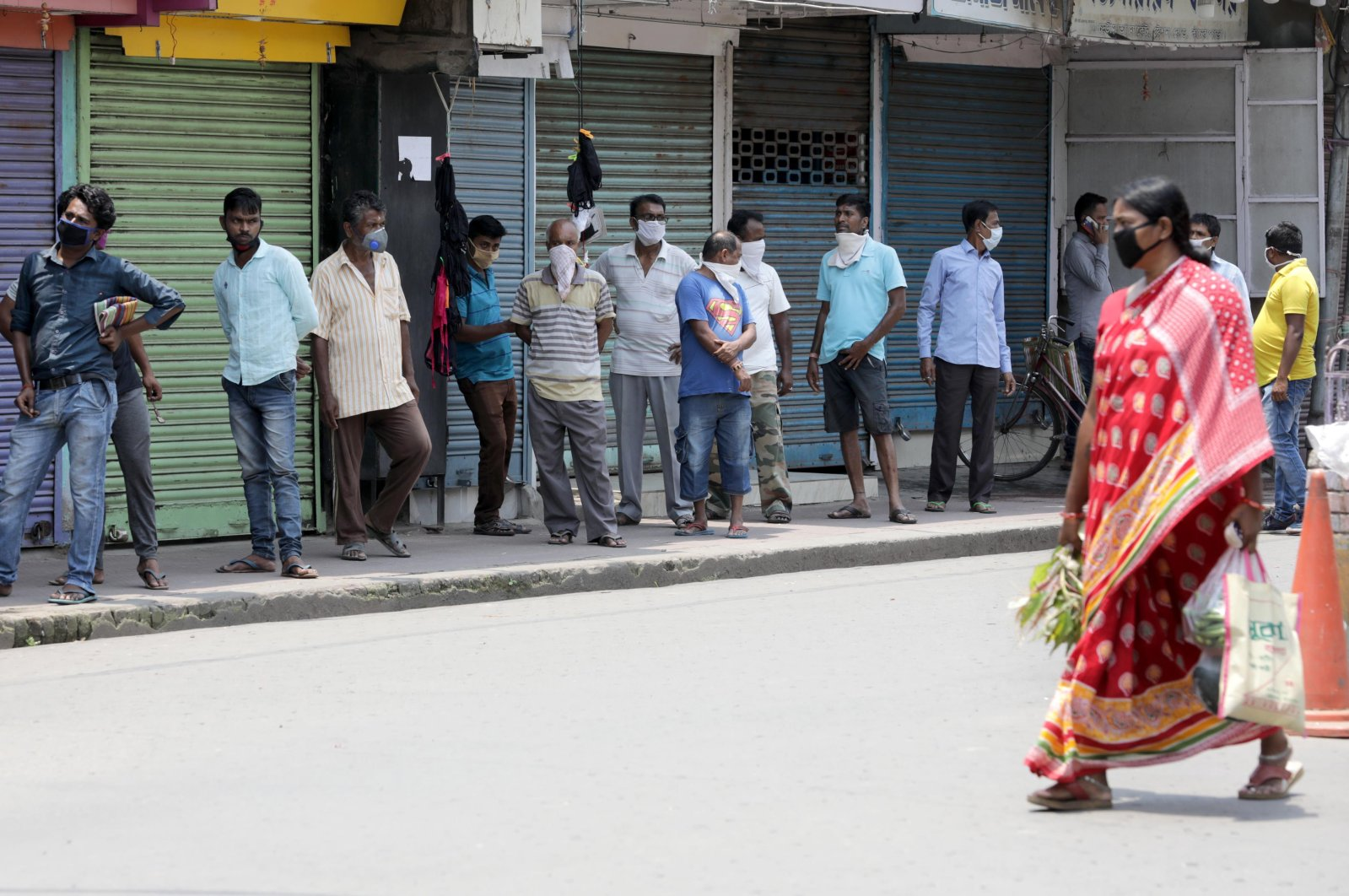 People wearing face masks queue up without keeping social distance outside a liquor store amid the ongoing coronavirus lockdown in Kolkata, India, May 5, 2020. (EPA Photo)