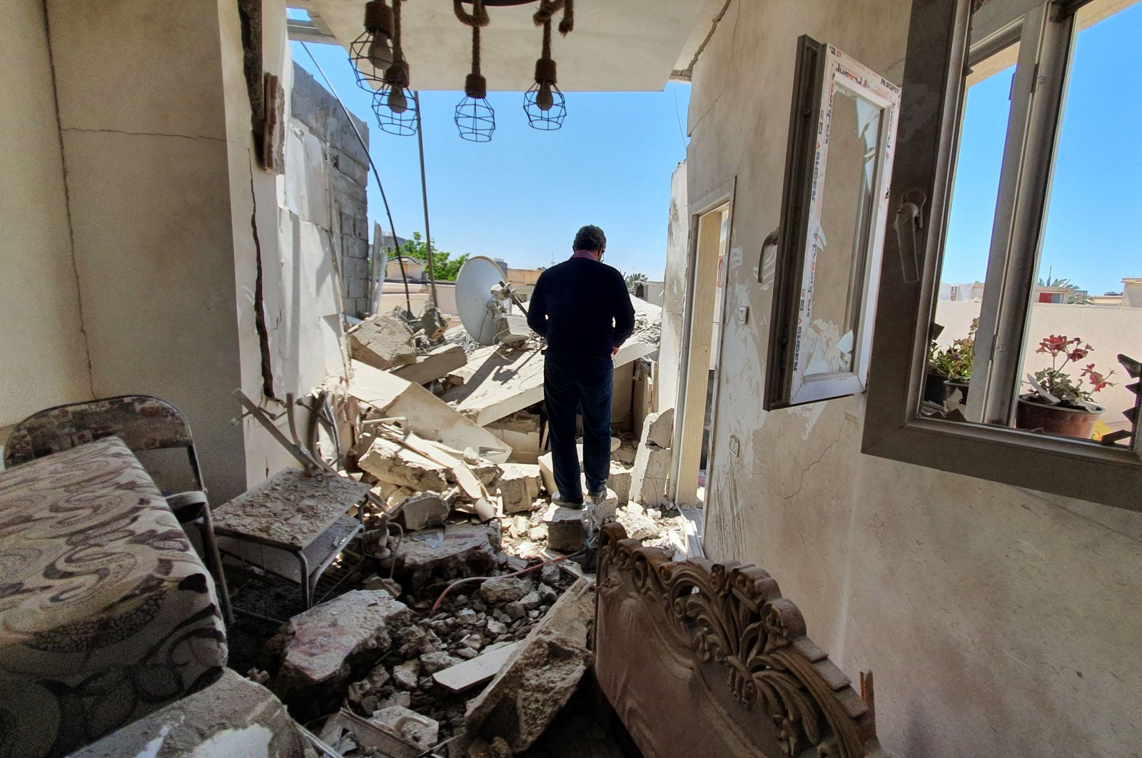 A resident walks amidst the rubble of a building that was damaged when putschist Gen. Khalifa Haftar's forces shelled the residential neighbourhood of Znatah in the Libyan capital Tripoli, held by the U.N.-recognized Government of National Accord (GNA), on May 1, 2020. (AFP Photo)