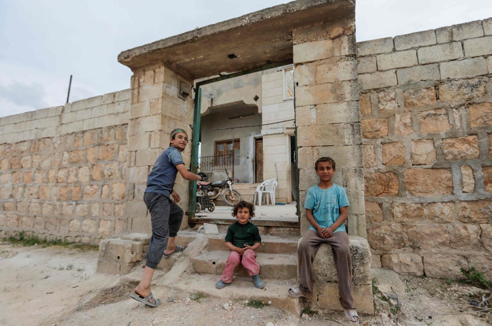 Syrian children whose family decided to return home, rest by the entrance as they clean the rubble from their house's yard in al-Nayrab, a village ravaged by regime forces bombardment near the M4 strategic highway, in Syria's northwestern Idlib province, May 3, 2020. (AFP Photo)