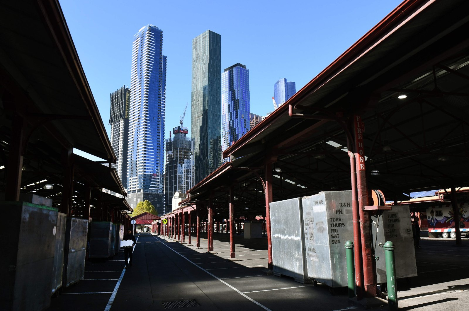 A man (L) walks through a deserted part of Melbourne's Queen Victoria Market, May 5, 2020. (AFP Photo)