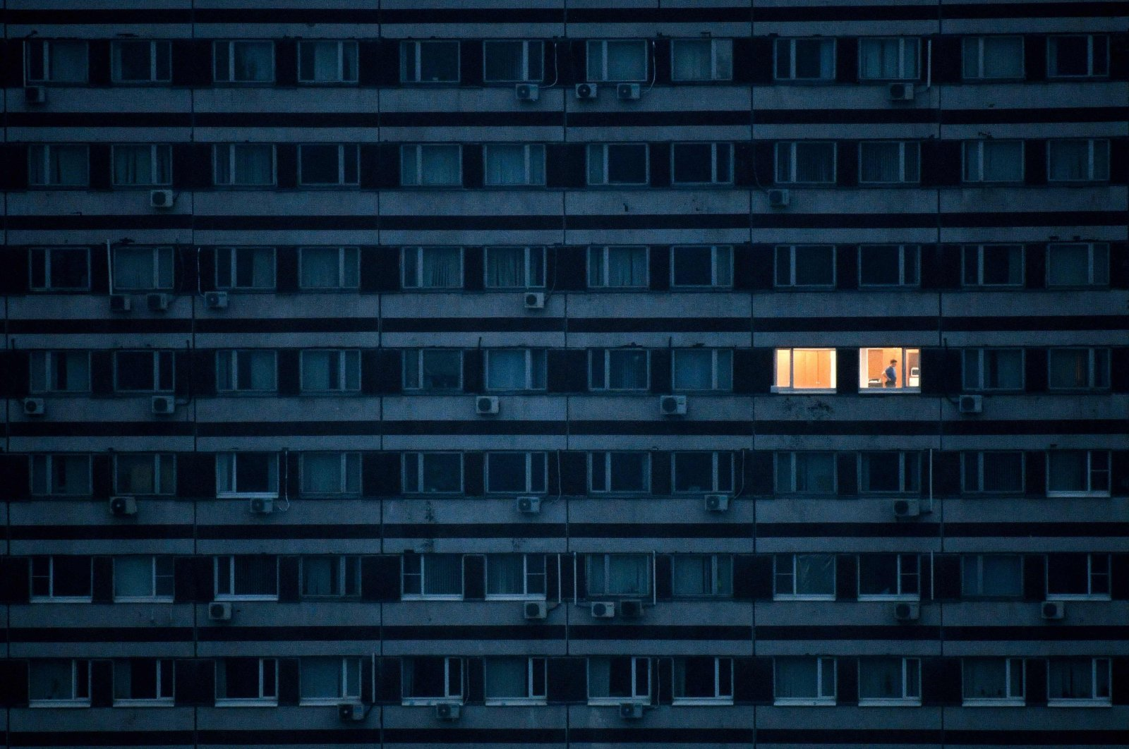 A man seen in an illuminated apartment in a building on the outskirts of Moscow during a strict lockdown in Russia to stop the spread of the new coronavirus, May 4, 2020. (AFP Photo)