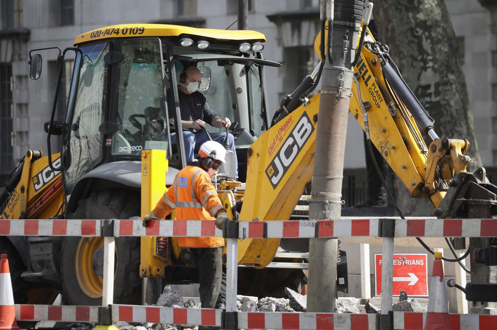 Workers wear face masks to protect against the coronavirus as they work on a road in London, May 4, 2020. (AP Photo)