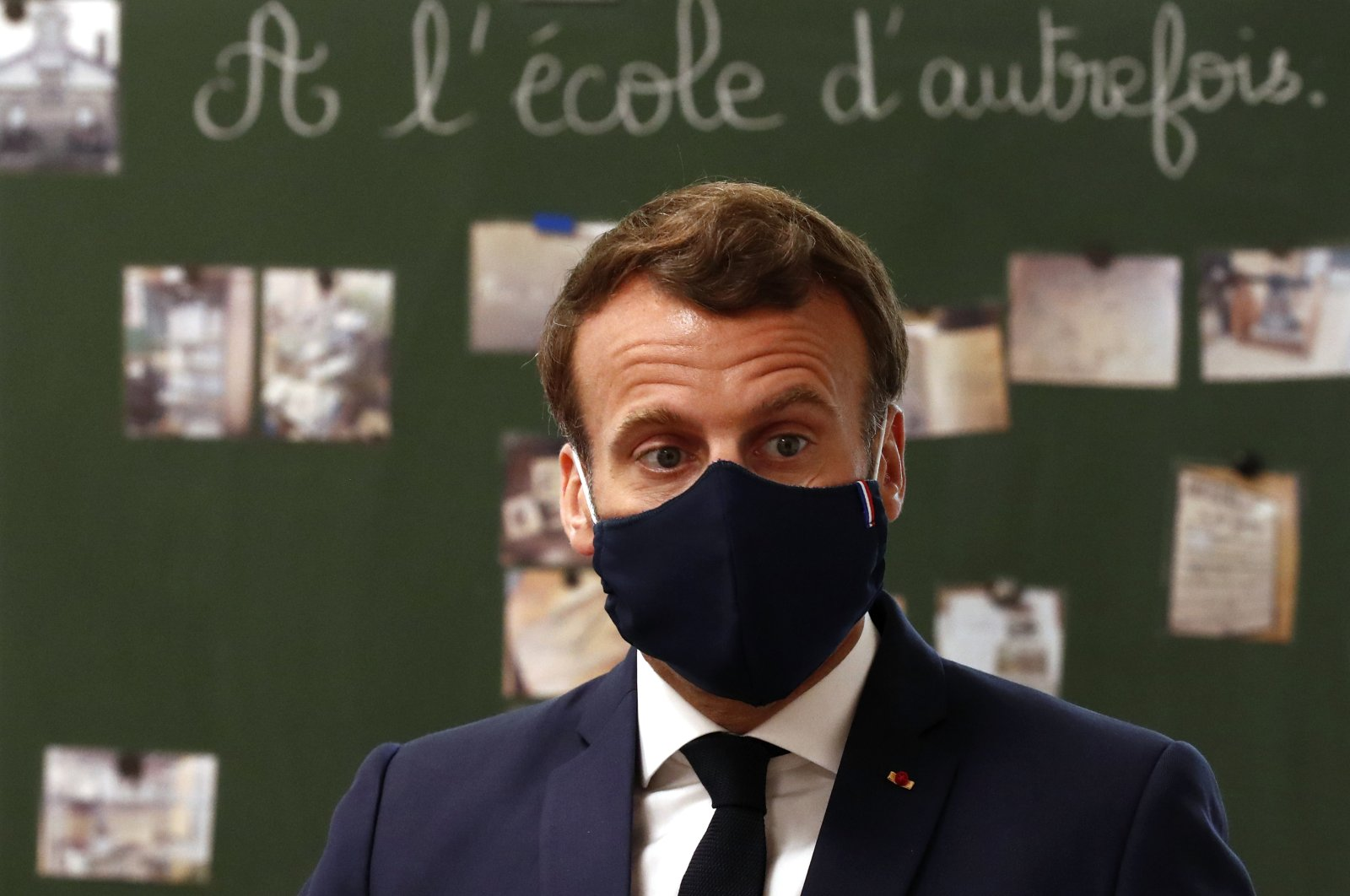 French President Emmanuel Macron, wearing a protective face mask, speaks with schoolchildren during a class at the Pierre Ronsard elementary school in Poissy, outside Paris, May 5, 2020. (AP Photo)