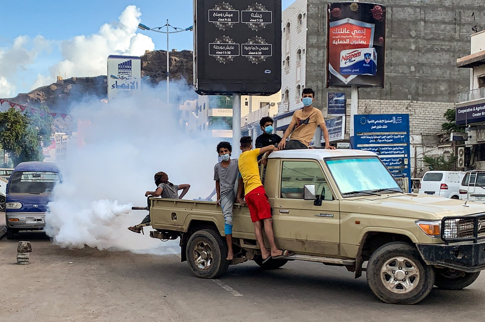 Youths wearing masks as a precaution due to COVID-19 coronavirus disease, sit in the back of a truck carrying out fumigation in an area in Yemen's southern coastal city of Aden, May 5, 2020.  (AFP)
