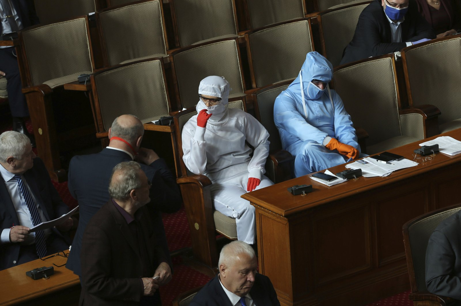 Vesselin Mareshki (R) leader of Bulgarian Political party Volya, and an MP from from his party wear protective suits during Parliamentary session in the Bulgarian National Assembly in Sofia, Bulgaria, March 20, 2020. (AP Photo)