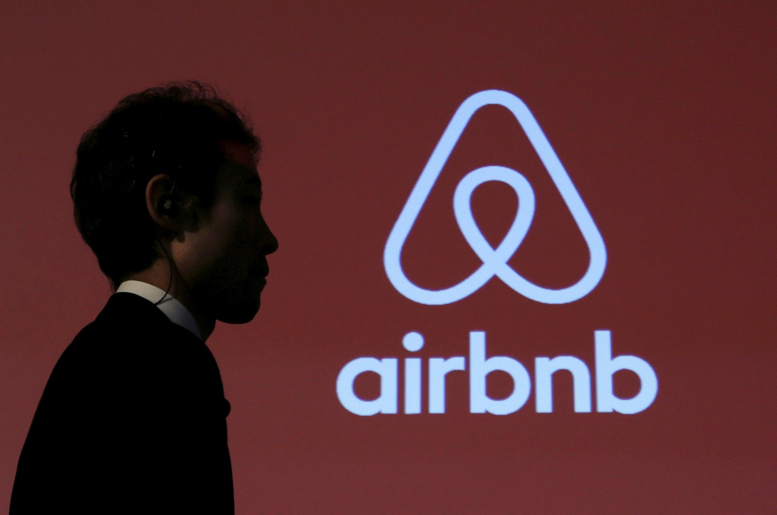A man walks past a logo of Airbnb after a news conference in Tokyo, Japan, Nov. 26, 2015. (REUTERS)