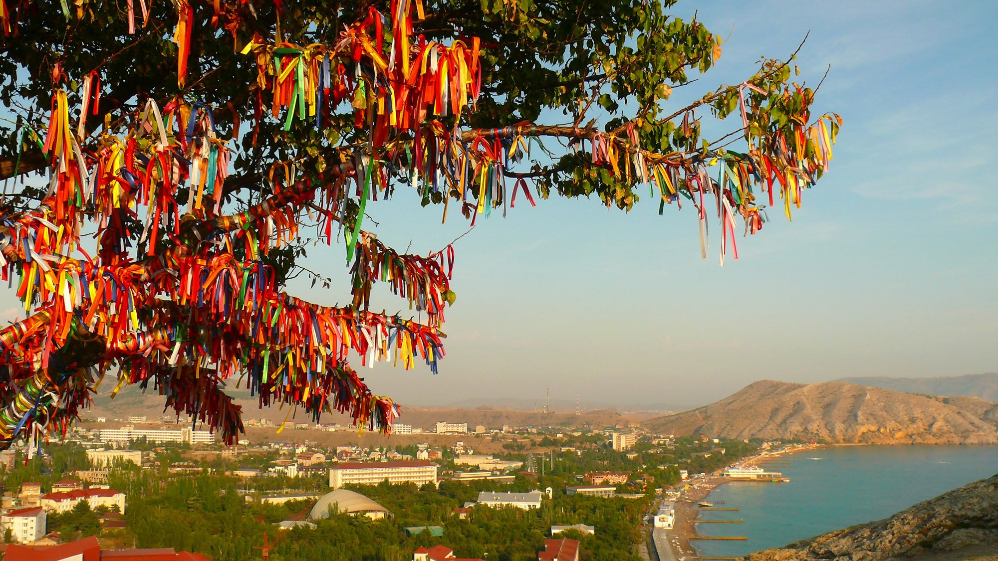 People tie clothes to the rose branches and trees for their wishes during Hıdırellez. (Shutterstock Photo)