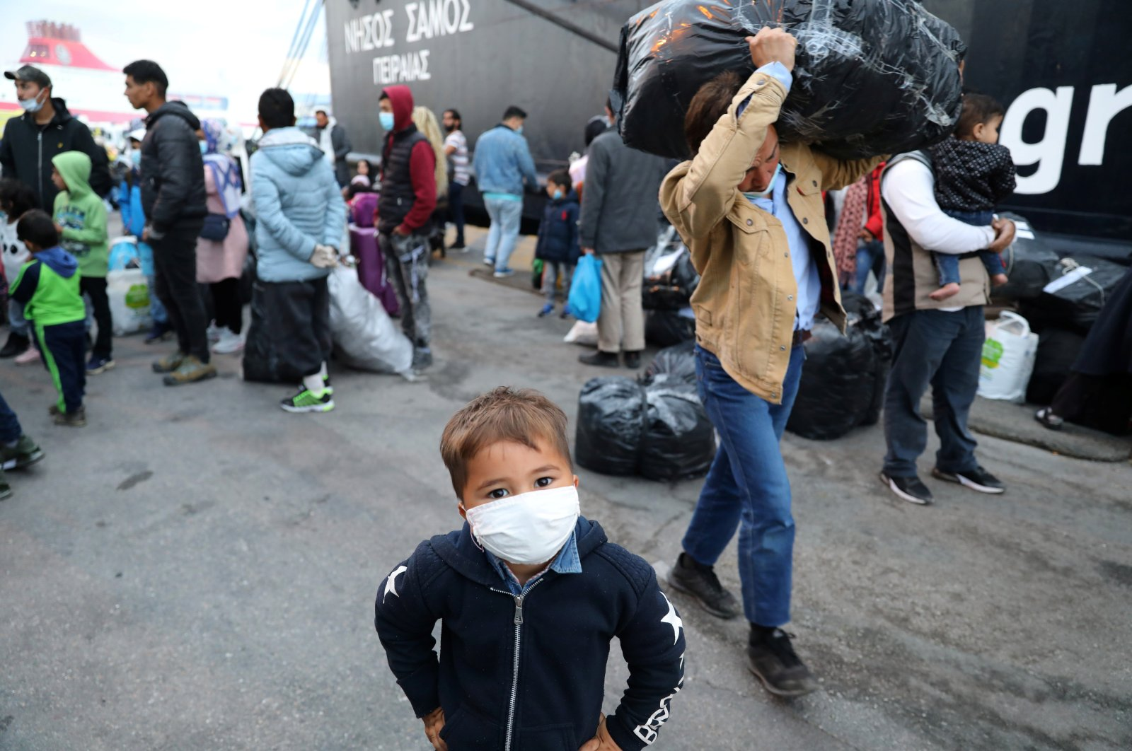 A migrant boy from the Moria camp in Lesbos waits to board a bus at Piraeus port in Athens following the coronavirus disease (COVID-19) outbreak, Greece, May 4, 2020. (Reuters Photo)