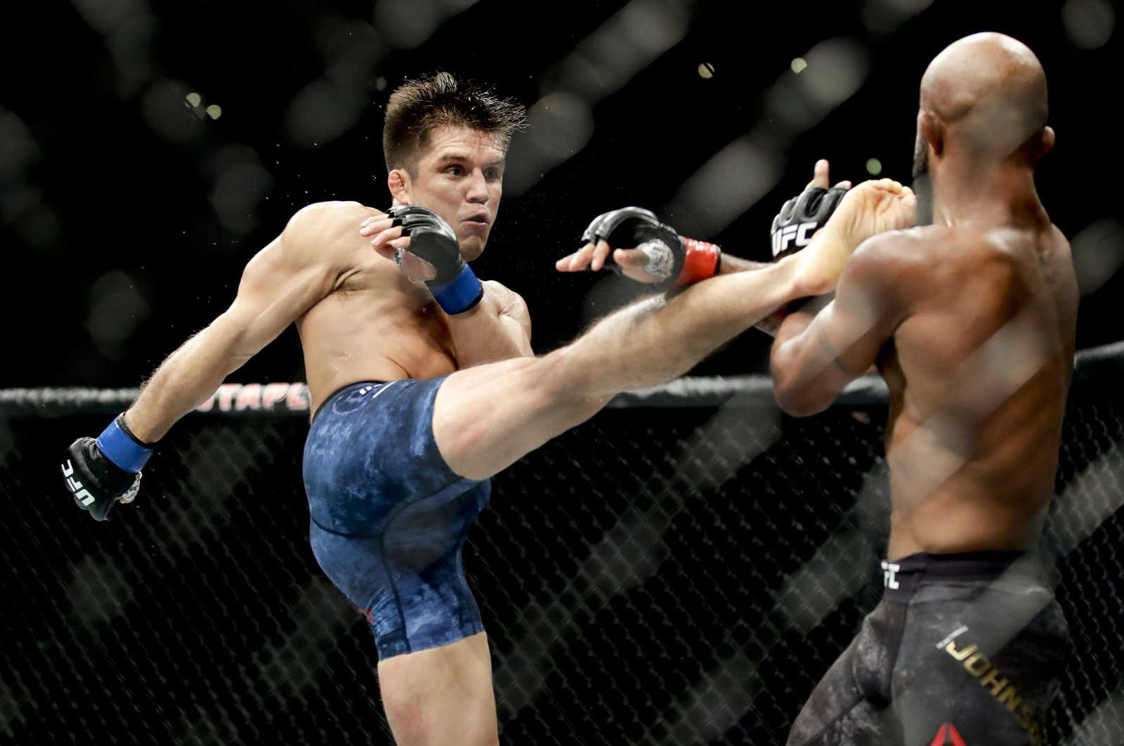 Henry Cejudo kicks Demetrious Johnson during their UFC flyweight title mixed martial arts bout at UFC 227 in Los Angeles, Aug. 4, 2018. (AP Photo)
