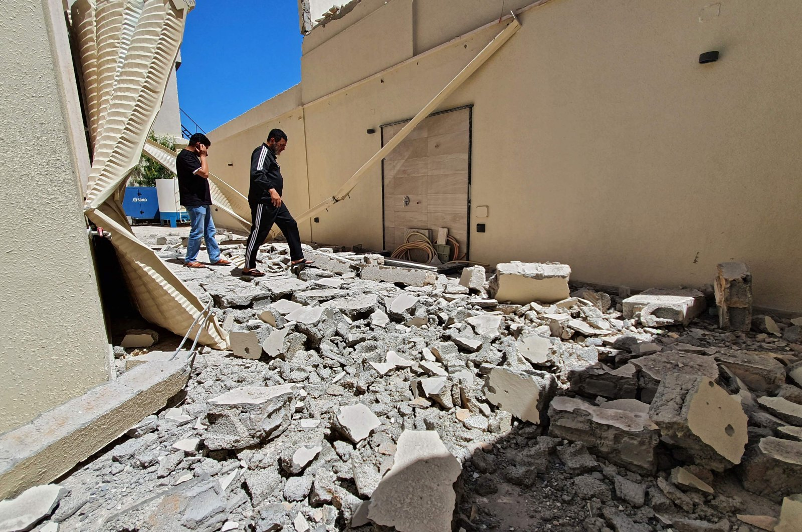 Residents walk amid the rubble of a building damaged when forces loyal to eastern-based warlord Khalifa Haftar shelled the residential neighborhood of Znatah in the Libyan capital Tripoli, held by the U.N.recognized Government of National Accord (GNA), May 1, 2020. (AFP Photo)