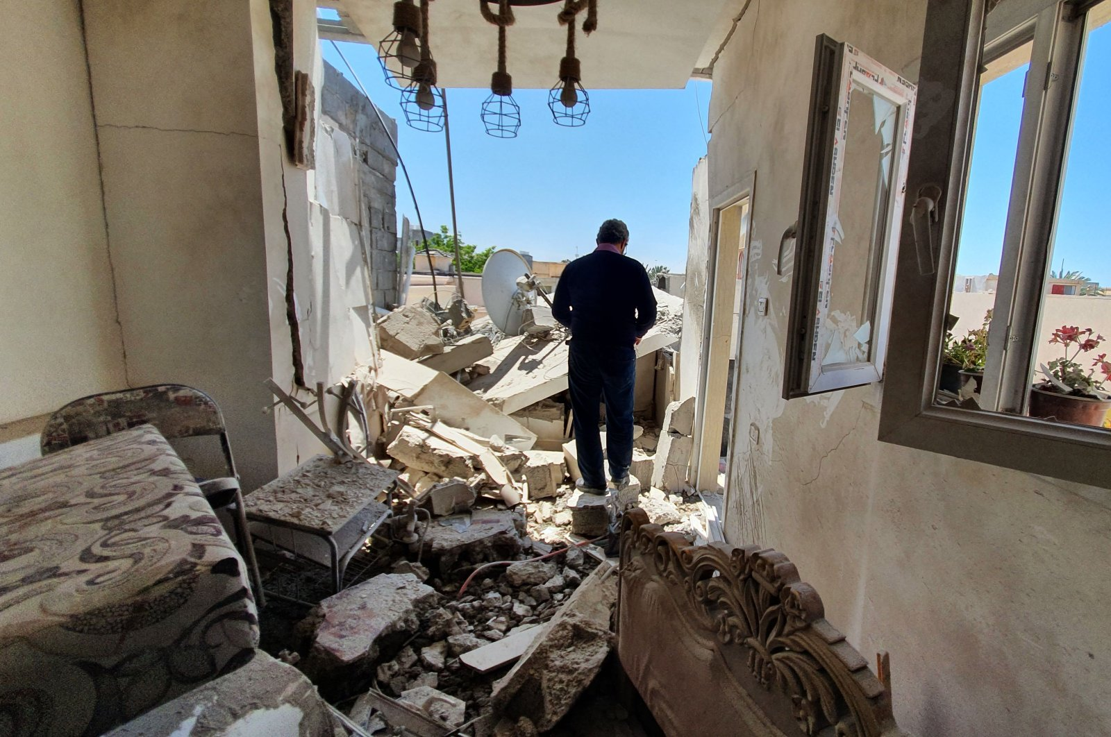 A resident walks amidst the rubble of a building that was damaged when forces loyal to eastern-based putschist Gen. Khalifa Haftar shelled the residential neighbourhood of Znatah in the Libyan capital Tripoli, May 1, 2020. (AFP Photo)