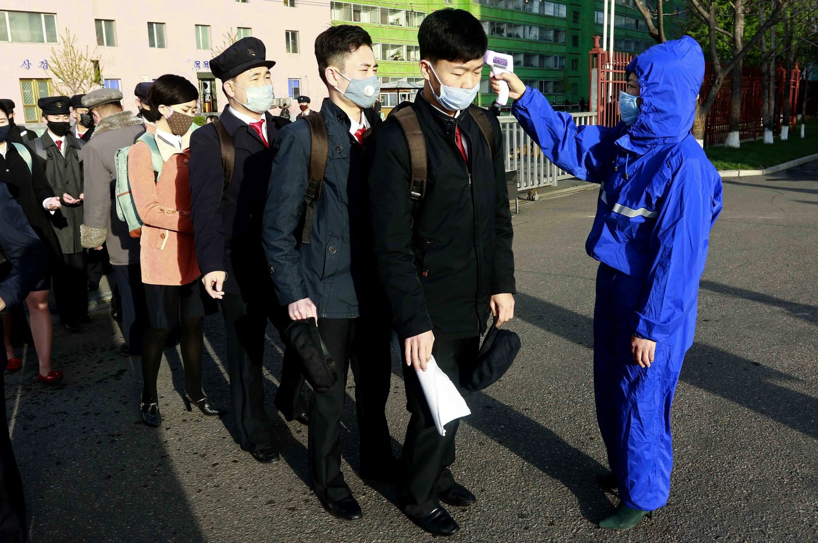 Students wearing face masks have their temperature checked as a precaution against the new coronavirus before returning to classes at Kim Chaek University of Technology, Pyongyang, North Korea, April 22, 2020. (AP Photo)