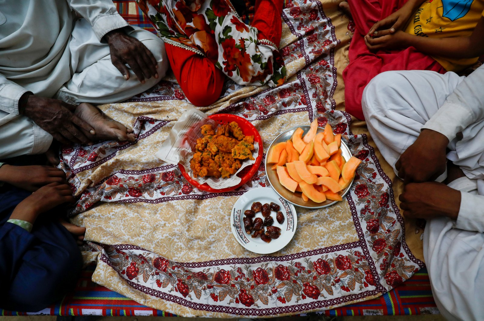 Fisherman Mohammad Sabir, 60, sits with his family as they wait to break their fast during the Muslim fasting month of Ramadan, amid the outbreak of the coronavirus disease (COVID-19), in Ibrahim Hyderi fishing village on the outskirts of Karachi, Pakistan April 30, 2020. (REUTERS Photo)
