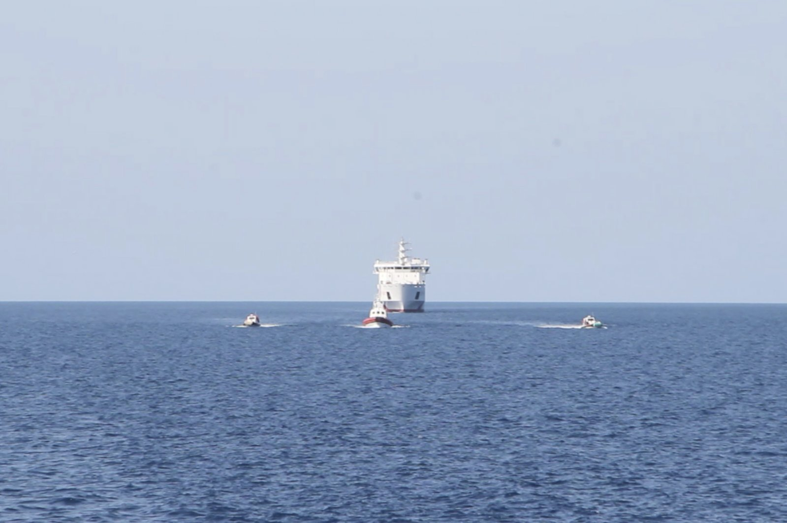 The Alan Kurdi rescue ship carrying migrants saved from sinking in the Mediterranean approaches a ferry, seen in the background's center, for a 14-day quarantine, April 17, 2020. (AP Photo)