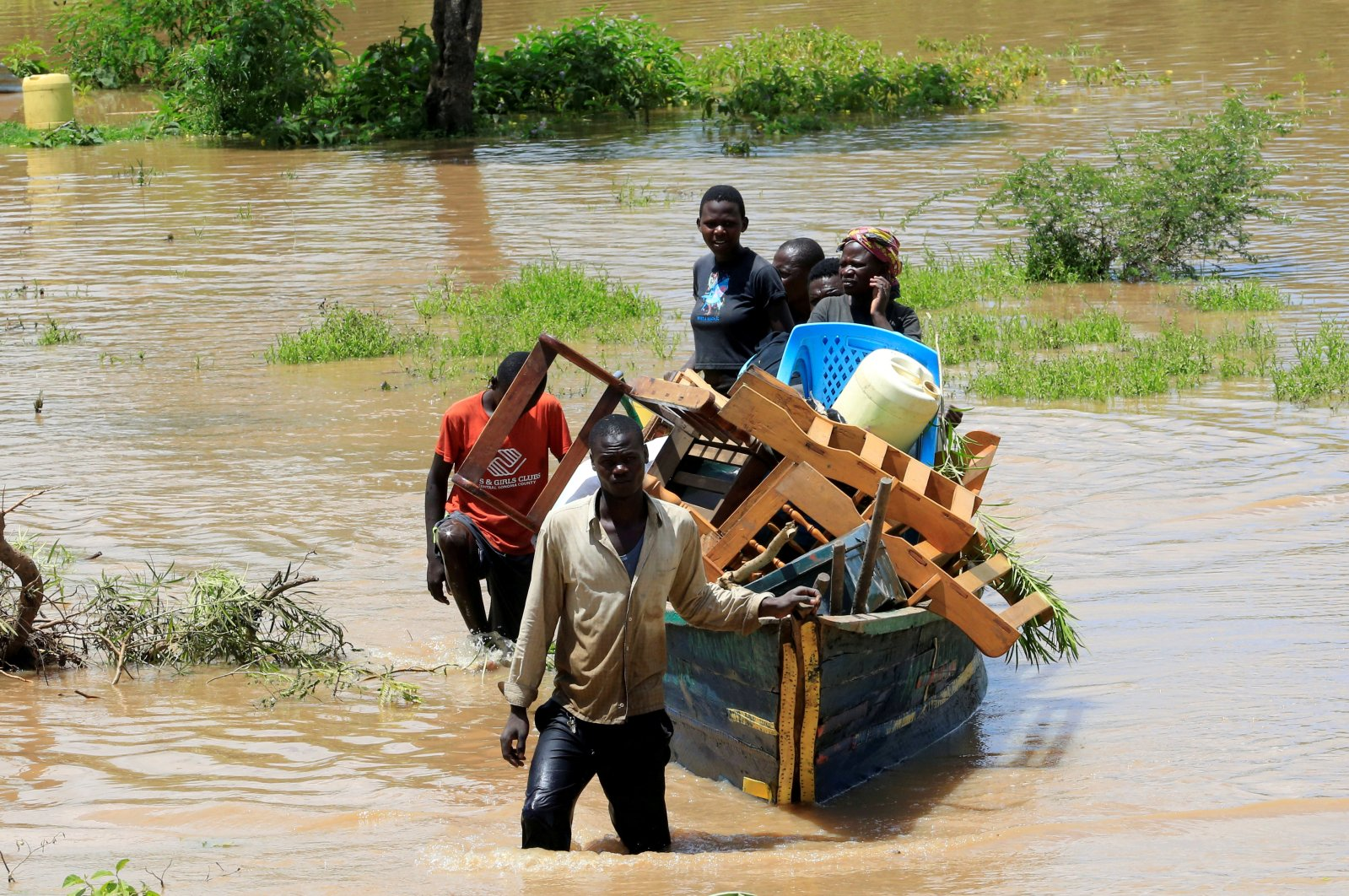 Residents use a boat to carry their belongings through the waters after their homes were flooded in Budalangi, in Busia County, Kenya, May 3, 2020. (Reuters Photo)